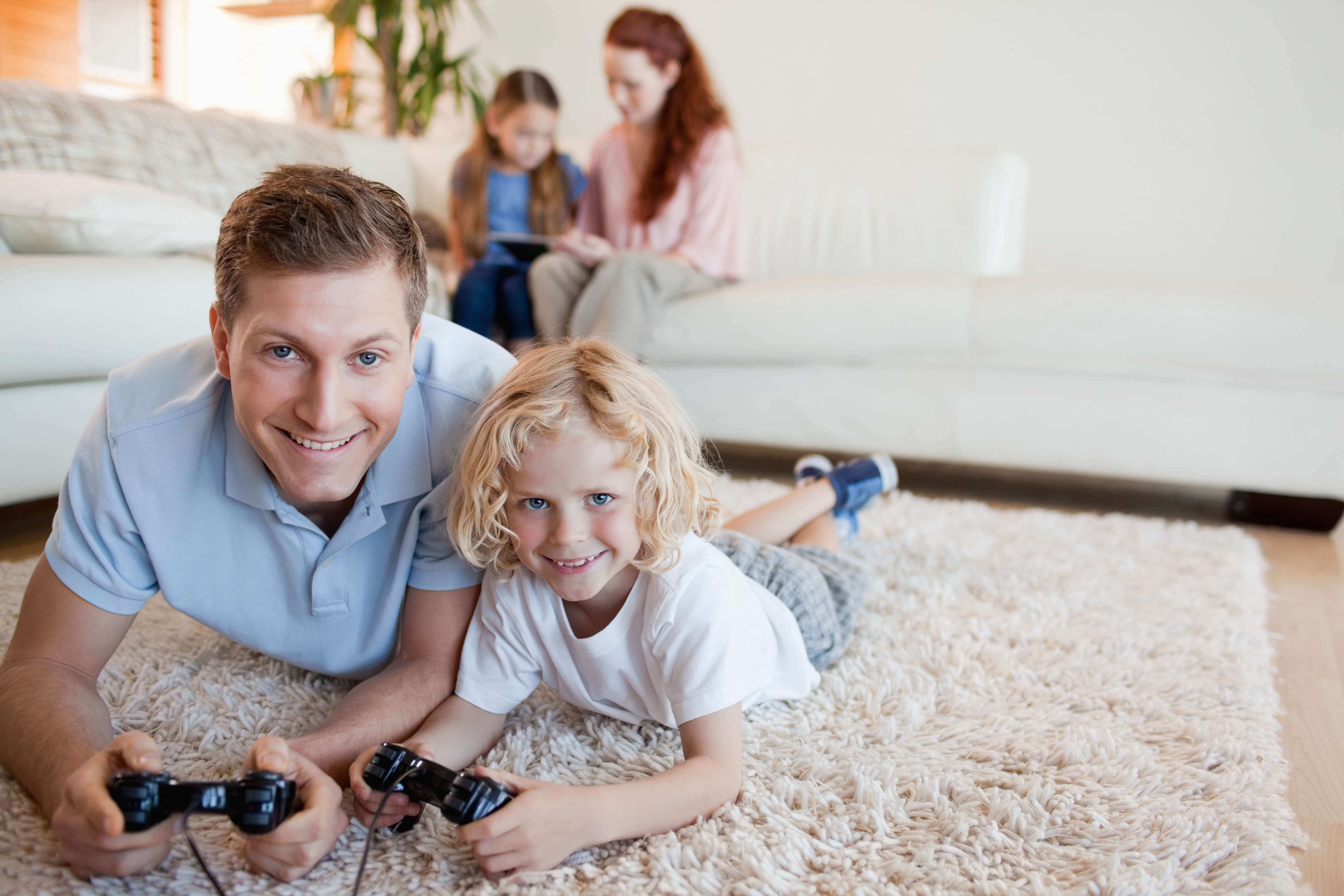 a father and son are playing video games while laying down on a carpet cleaned by Green Leaf Chem-Dry