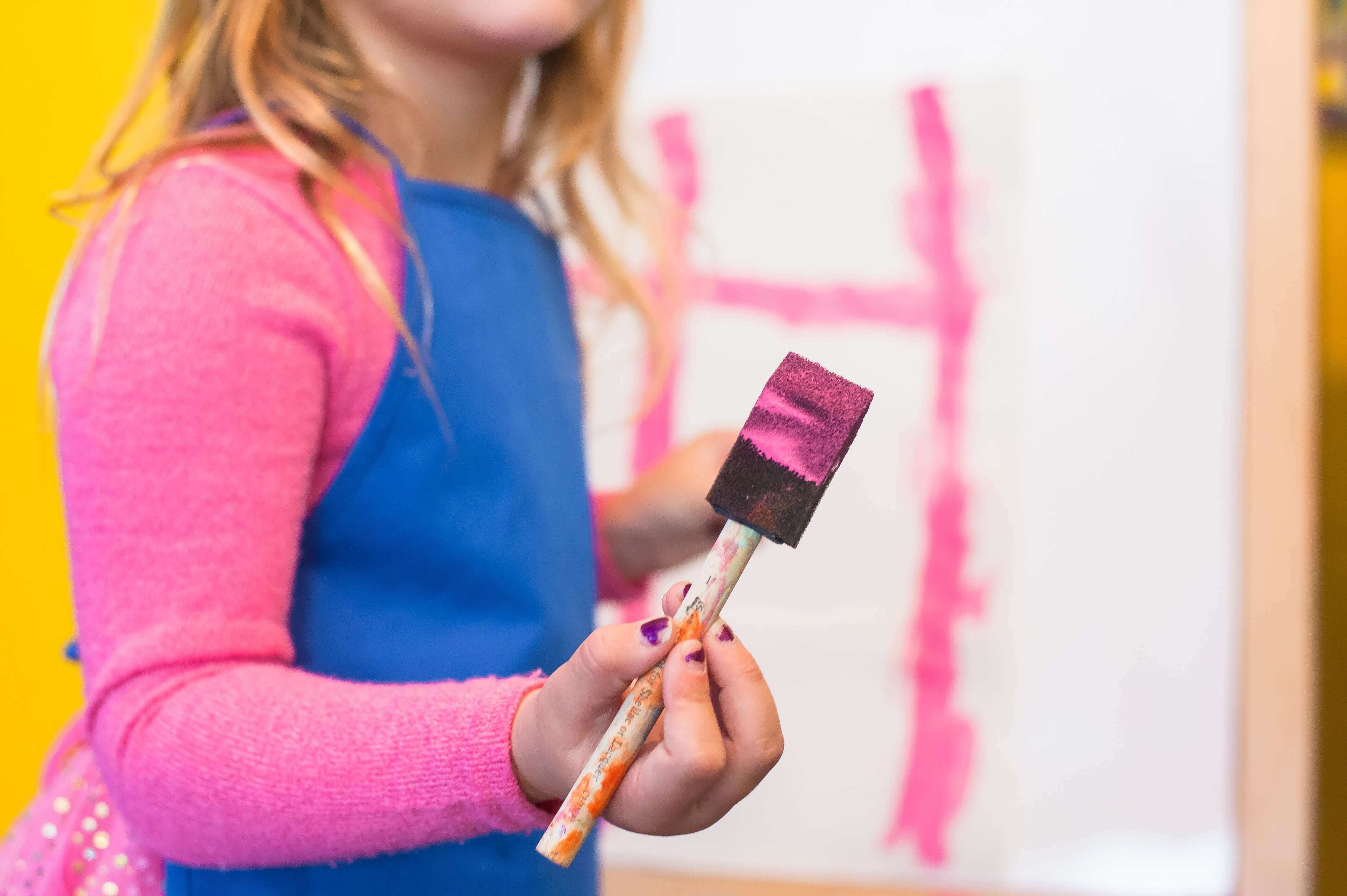 a little girl painting with pink paint.